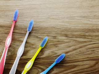 top view toothbrushes on wooden background with space copy