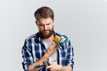 Young guy with a beard on a white isolated background holds tools for repair