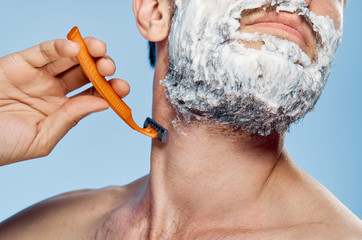 Young guy with a beard on a blue background shaves