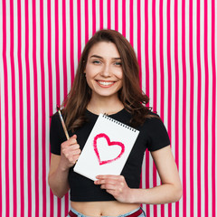 Smiling girl holding otepad and brush