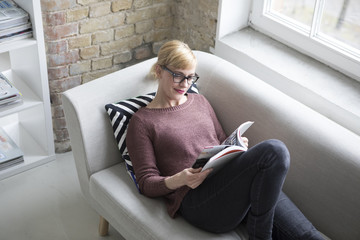 Woman sitting on couch, reading book