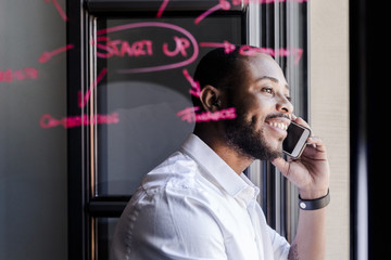 Smiling businessman on cell phone in office with writing on windowpane