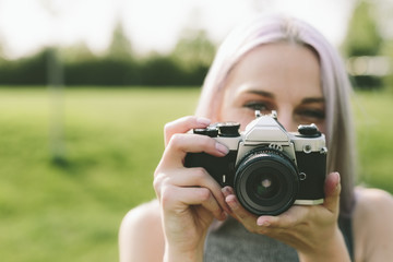 Young woman taking pictures with camera in nature
