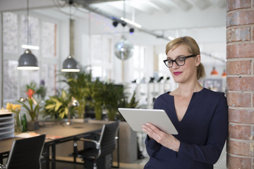 Portrait of a businesswoman in office, using digital tablet