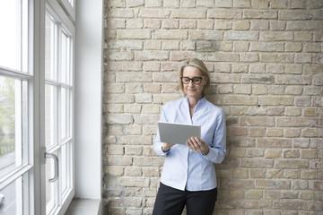 Mature businesswoman using digital tablet