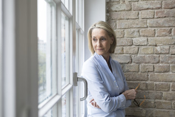 Mature businesswoman standing at window, looking worried