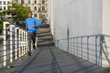 Young man running on footbridge in the city