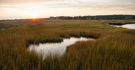 Sunset on Cape Cod with tide pool and marsh grasses in foreground.