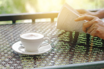 Stock photo :.Cappuccino coffee cup on a table with background of a businessman reading a newspaper in the morning light.