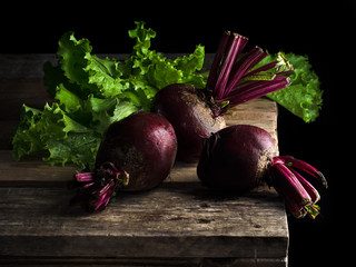 Red buryak on a wooden background with a green salad