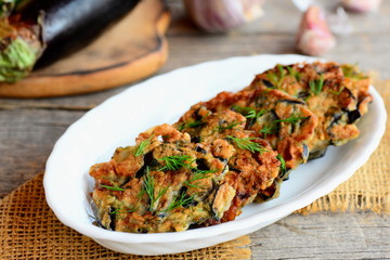 Roasted eggplant cutlets. Crispy eggplant fritters with garlic and dill on a white plate and a vintage wooden table. Creative vegetarian eggplant recipe. Closeup