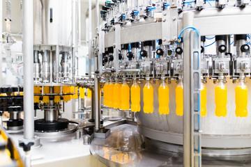 Bottling factory - Orange juice bottling line for processing and bottling juice into bottles. Selective focus.