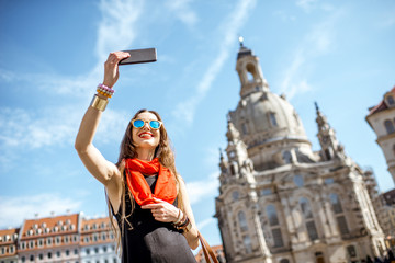 Young elegant woman tourist making selfie photo in front of the famous church in Dresden city, Germany