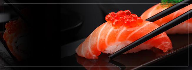 Japanese cuisine. Salmon sushi nigiri in chopsticks over black background.