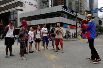 Demonstrators sing the national anthem next to violinist Wuilly Arteaga while blocking a street during a protest against Venezuelan President Nicolas Maduro's government in Caracas