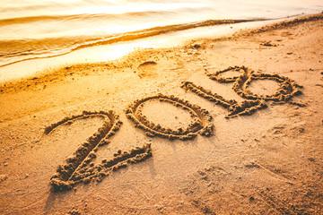 Year 2018 handwritten on seashore sand.