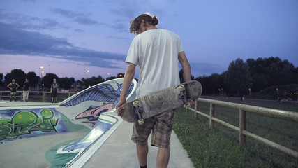 Closeup of young adult from behind walking with his skateboard at skate park.