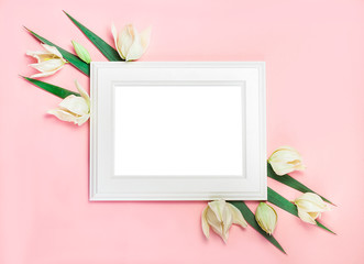 white wooden frame on pink background decorated with green leaves, blank space for a text. Top view, flat lay