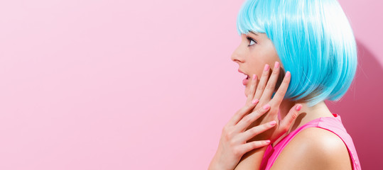 Wall Mural - Portrait of a woman in a bright blue wig on a pink background