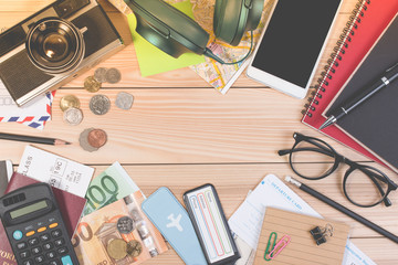 Traveler object, passport, euro coin, euro banknote, headphones, passport, touristic map. Top view travel or traveler supplies on office wooden desk table. Travel concept on wooden table.