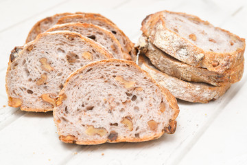 Slices of walnut bread on white wooden background