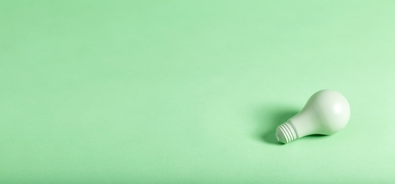 Green energy theme with green light bulb on a green background