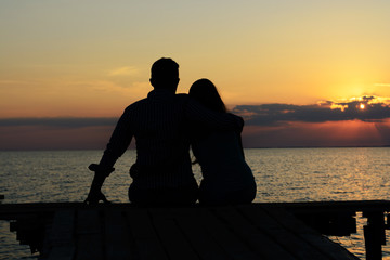 Two (pair) of lovers (girl and boy) sit on the dock in an embrace and look at the dawn (sunset) by the sea. Love and romance. Date.