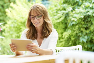 Working from home. Shot of  a happy middle aged woman using digital tablet while relaxing outdoor.