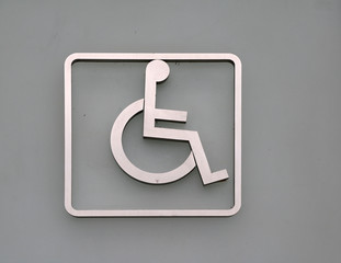 Handicapped mark on the door in front of the Bathroom disabled. who having a physical or mental condition that limits movements or activities.