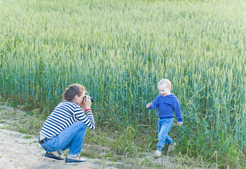 Young woman taking pictures of a child in a field