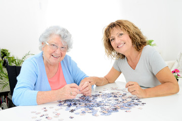 cheerful mature woman doing puzzle and spending time with elderly senior woman at home