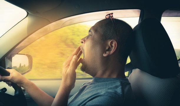 Sleepy yawning man driving car in traffic after long hour drive. Man falling asleep in car.