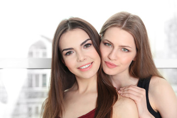 Lovely lesbian couple hugging on blurred background