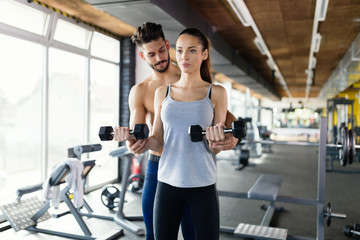 Young woman doing exercises in gym with trainer