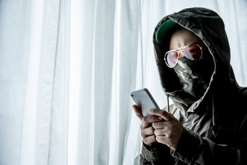 Hacker or terrorists  in hood with masked working on dark digital his on with cell telephone or smartphone for bomb . Hacking the system cyber crime concept .
