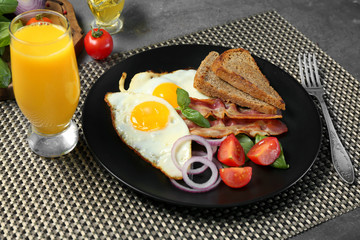Delicious over easy eggs with vegetables and bacon on kitchen table