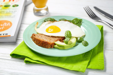 Delicious over easy egg with bread, avocado and basil leaves on kitchen table