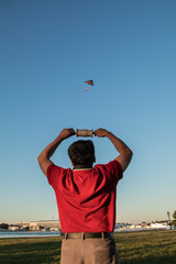 An adult flying kite in the sky