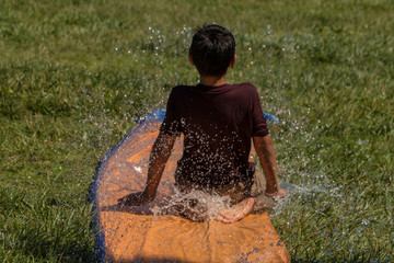 Young boy sliding in water