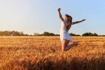 Beautiful young girl in white dress jumping in  wheat field