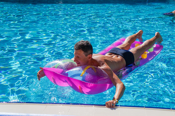 A man enjoys in the sea. Man floating on a mattress in water pool.
