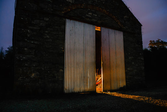 Light shines out from half open doors of an old Irish stone barn at night
