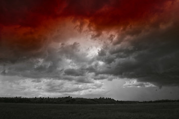 Storm cloud over fields forests and hills