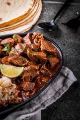 Mexican and American traditional food. Stew beef with tomatoes, spices, pepper - Chile Colorado. With boiled rice. lime, tortillas.  Copy space. On black stone table