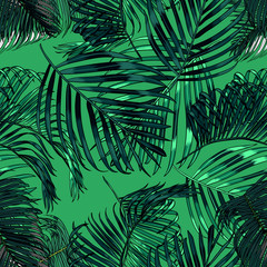 Palm leaves silhouette on the green background. Vector seamless pattern with tropical plants.