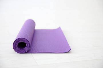 Purple yoga mat on light background