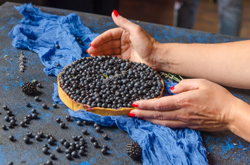 Woman hands holding french homemade tart with blueberries . Top view