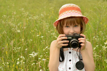 portrait of a baby photographer (a little girl) with a camera on the background of nature