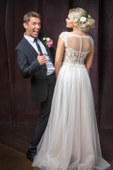 bridegroom rejoices in his wedding next to the bride in the Studio