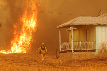 A firefighter walks near a home as flames from the fast-moving Detwiler fire approach in Mariposa